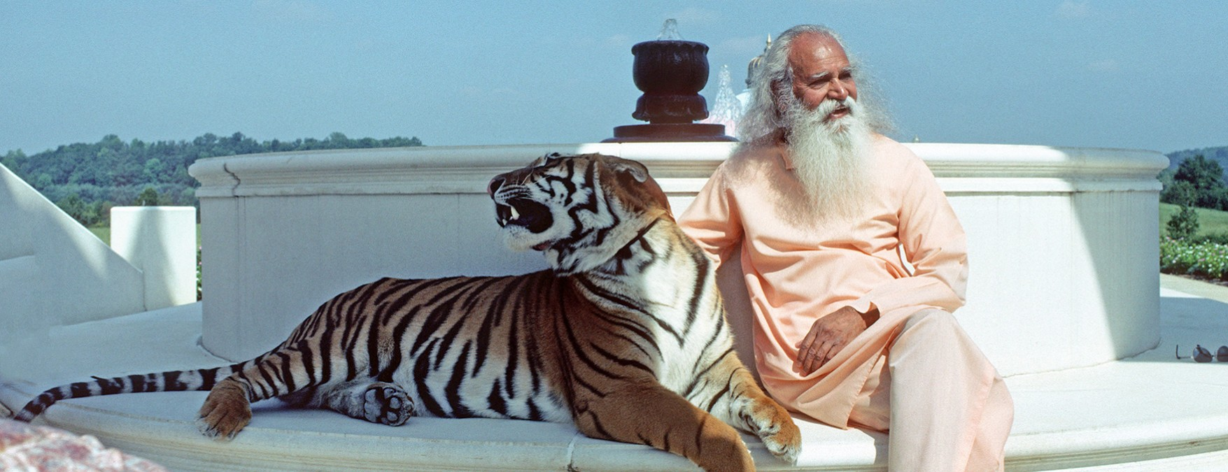 Swami Satchidananda sits with a tiger at the LOTUS